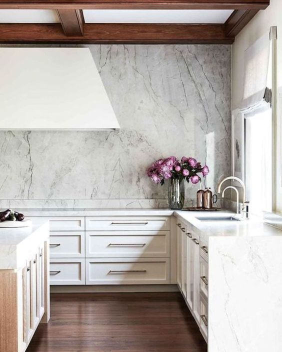 a very chic neutral kitchen with large white cabinets, white marble walls and countertops, a large hood and a coffered ceiling