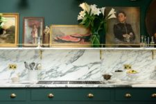 a very elegant and chic vintage kitchen in hunter green, with a white marble backsplash and touches of gold