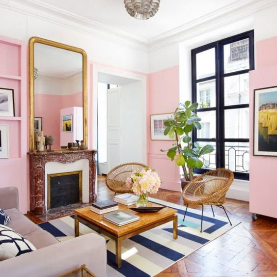 a vibrant living room with light pink walls, a colorful rug, a chic fireplace and a statement mirror is lovely