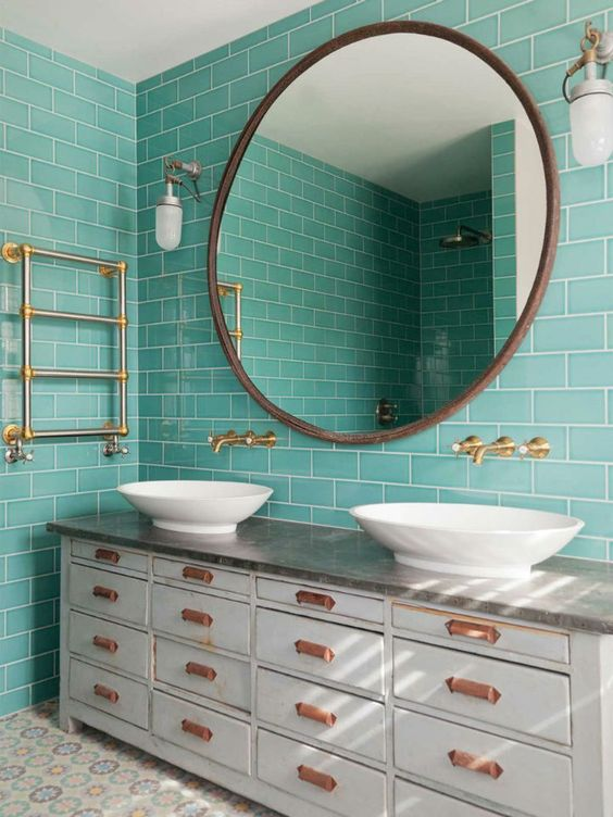a vintage bathroom clad with turquoise tiles, a large vintage vanity, white sinks, a round mirror and gold fixtures for a chic look