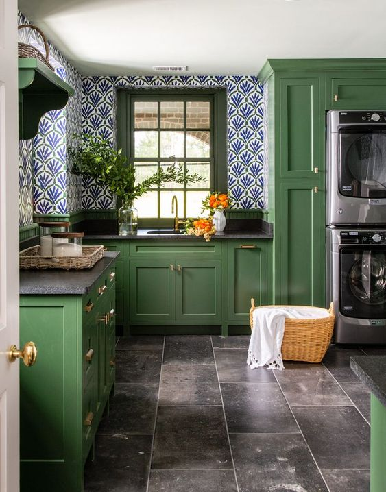 a vintage green kitchen with black countertops, bright wallpaper walls and built in washers
