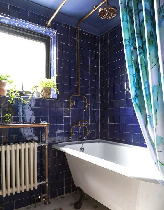 a vintage-inspired bathroom with bold blue Zellige tiles, a vintage radiator and bathtub, brass touches