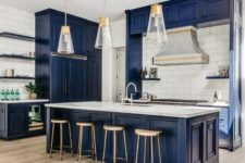 a vintage-inspired bold blue kitchen with a white tile backsplash, white stone countertops, pendant lamps and wooden stools