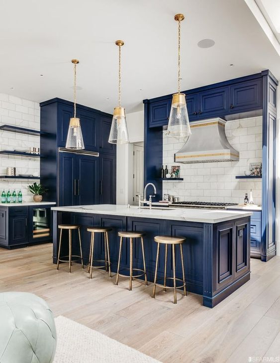 a vintage inspired bold blue kitchen with a white tile backsplash, white stone countertops, pendant lamps and wooden stools