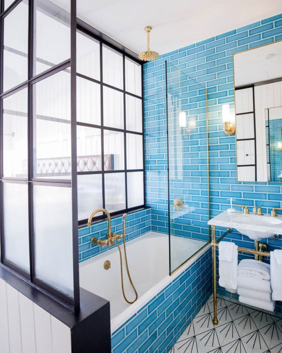a vintage-inspired bright blue bathroom with a vintage sink and touches of gold here and there