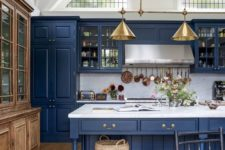 a vintage-inspired kitchen in classic blue, with a white marble backsplash and countertos plus gold lamps
