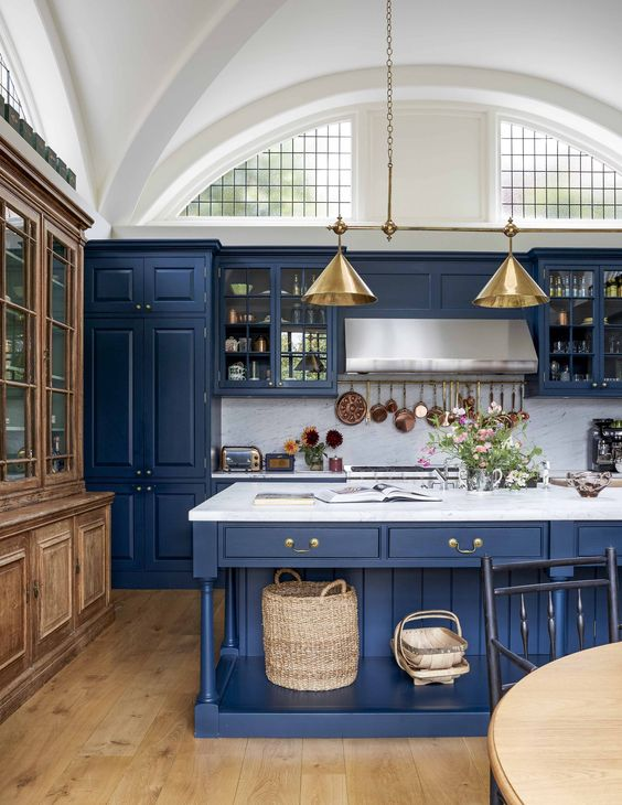 a vintage inspired kitchen in classic blue, with a white marble backsplash and countertos plus gold lamps