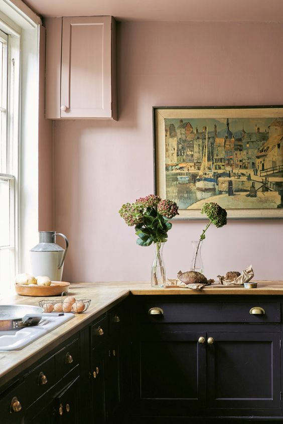 a vintage-inspired kitchen with blush walls, black cabinets, butcherblock countertops and gold handles plus a statement artwork