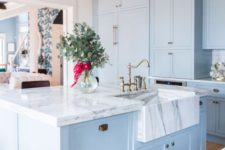 a vintage-inspired light blue kitchen with a white marble countertop and a brass pendant lamp