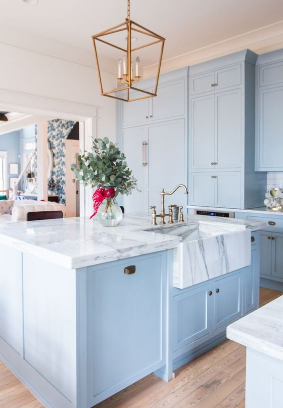 a vintage inspired light blue kitchen with a white marble countertop and a brass pendant lamp