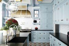 a vintage-inspired light blue kitchen with black countertops, a white tile backsplash, potted plants and a vintage hood