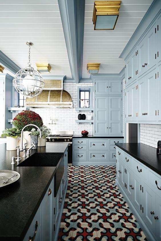 a vintage inspired light blue kitchen with black countertops, a white tile backsplash, potted plants and a vintage hood