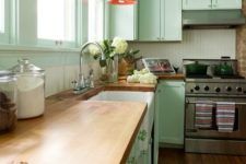 a vintage-inspired mint green kitchen with butcherblock countertops, pink pendant lamps and a white beadboard backsplash