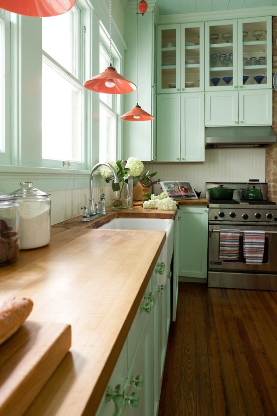 a vintage inspired mint green kitchen with butcherblock countertops, pink pendant lamps and a white beadboard backsplash