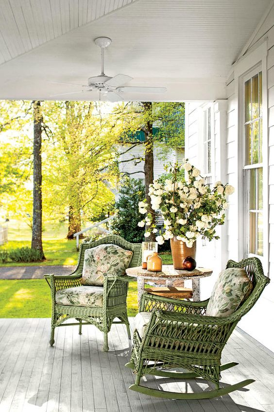 a vintage-inspired summer porch with green wicker furniture, floral upholstery, a vintage table and lots of blooms