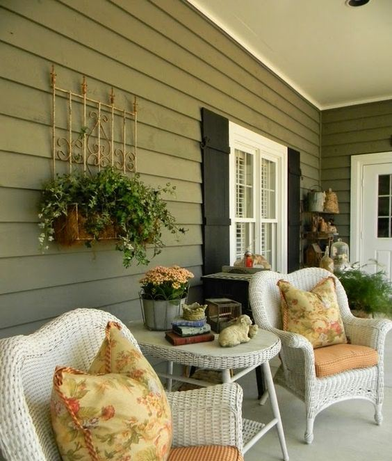 a vintage summer porch with white wicker furniture, printed pillows, potted greenery and blooms is chic
