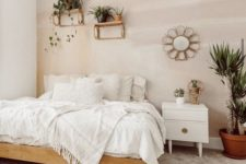 a warm neutral bedroom with an accent pastel wall, a wooden bed, a white nightstand, lots of potted plants