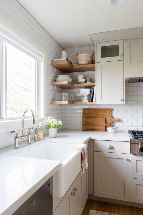 a warm neutral kitchen with white subway tiles, white countertops, touches of brass and built-in shelves