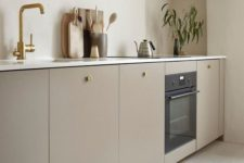 a warm neutral minimalist kitchen with sleek lower cabients, one upper, white countertops and brass touches