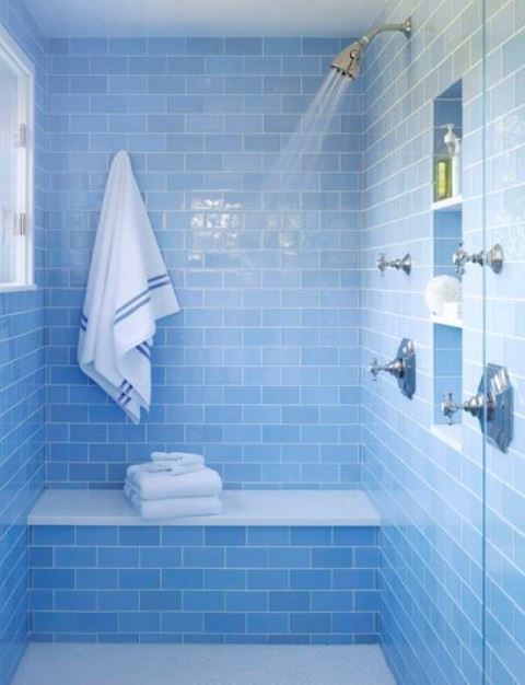 a watery blue bathroom fully clad with tiles and touches of neutral metallics for a chic and shiny look