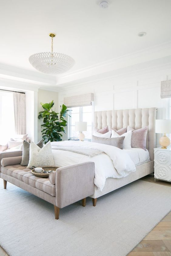 a welcomign modern neutral bedroom with a creamy bed, white nightstands, a grey bench, neutral curtains and a statement plant