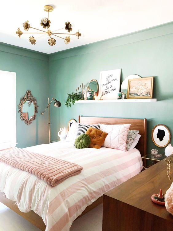 a welcoming bedroom with green walls, wooden furniture, a ledge as a gallery wall and gold and brass lamps