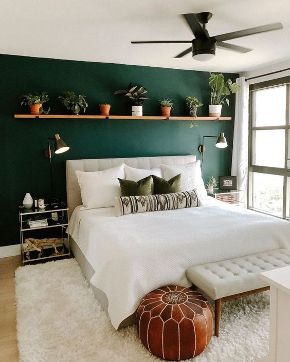 a welcoming boho bedroom with a forest green wall, neutral furniture, a shelf with potted greenery
