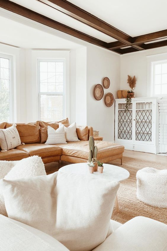 a welcoming boho living room with dark beams, a leather sofa, white furniture and decorative baskets on the wall