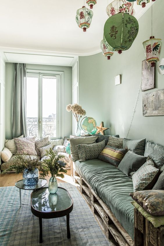 a welcoming green living room with light green walls, curtains, a hunter green sofa and pillows, a printed rug and pendant lamps