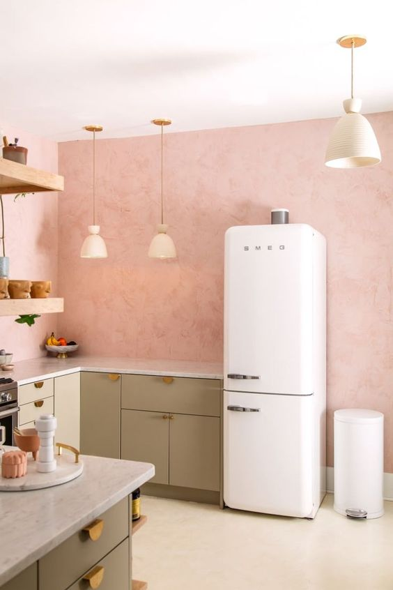 a welcoming kitchen with pink walls, green cabinets, gold handles, pendant lamps and open shelving