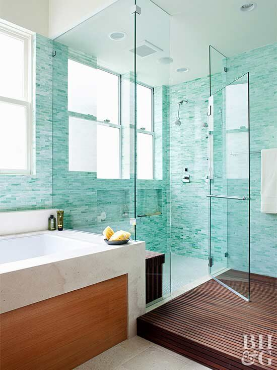 a welcoming modern bathroom with neutral stone, turquoise tiles, a dark wooden slab, several windows for much natural light