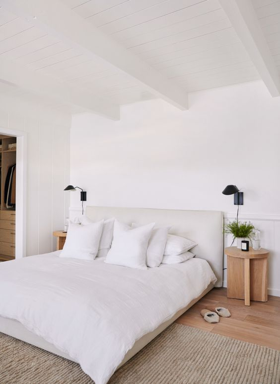 a welcoming neutral bedroom with a white bed, wooden bedside tables, black sconces and a soft rug
