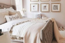 a welcoming neutral bedroom with blush walls, a grey upholstered bed, a gallery wall and soft layered bedding