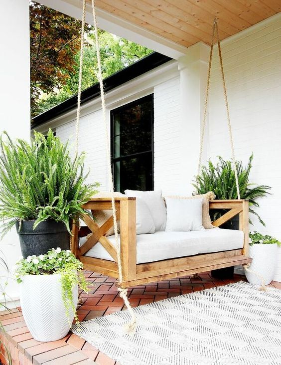 a welcoming neutral front porch with a wooden hanging bench, a neutrla rug and lots of potted greenery