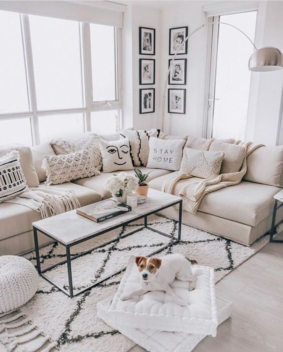 a welcoming small living room with a grey sectional, a marble coffee table, white cushions and a floor lamp