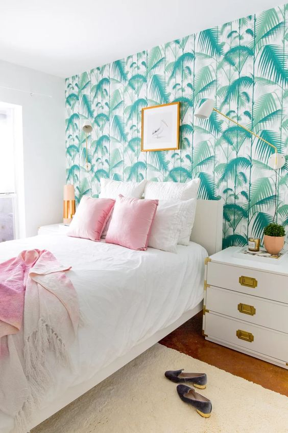 a welcoming tropical bedroom with a tropical leaf wall, white and gold furniture, pink bedding and touches of gold
