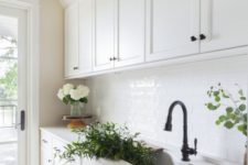 a welcoming white kitchen with white subway tiles, a white countertop, black fixtures and some blooms and greenery