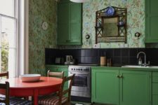 a whimsical retro bright green kitchen with catchy wallpaper walls, a black tile backsplash and a tiled floor