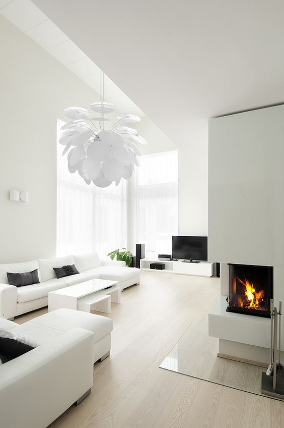 a white minimalist living room with simple and comfy furniture, a built-in fireplace, a petal lamp and much natural light