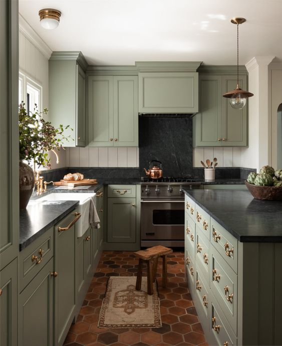 an English cottage kitchen in pale green, with black stone countertops and touches of brass and copper