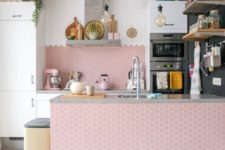 an airy kitchen with white cabinets and a large pink hex tile backsplash and kitchen island is really amazing