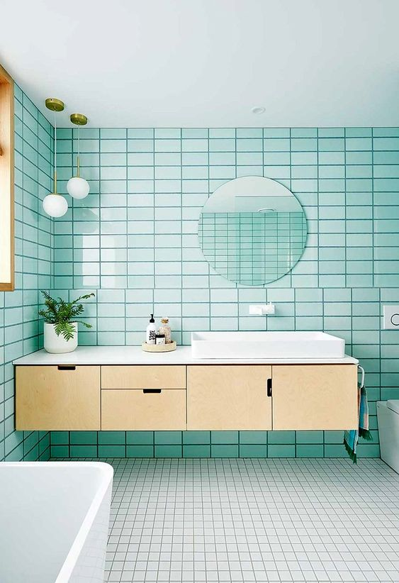 an airy modern bathroom with turquoise tiles, white on the floor, a floating plywood vanity and white appliances