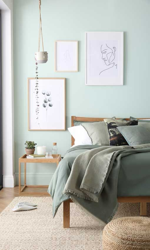 an airy monochromatic bedroom with light green walls, green bedding, a gallery wall and wooden furniture