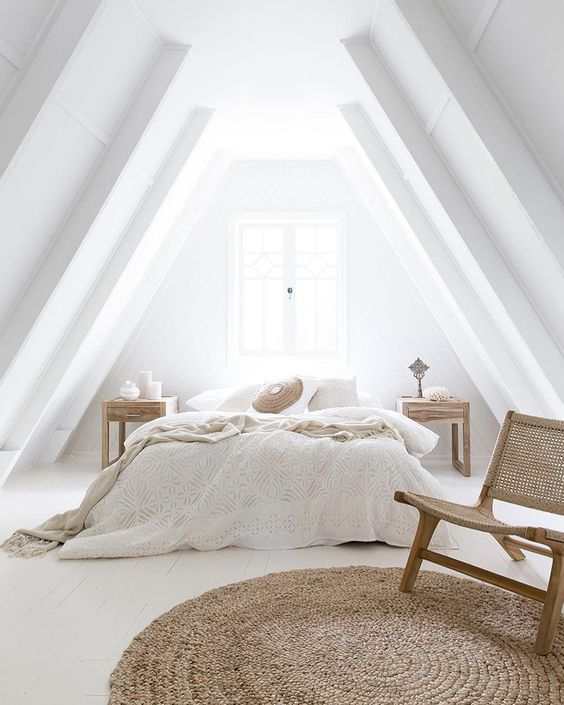 an airy neutral attic bedroom with a bed, wooden nightstands, a woven chair and a jute rug plus neutral bedding