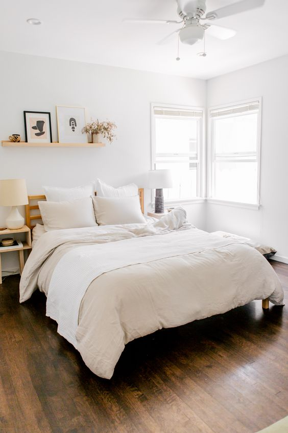 an airy neutral bedroom with a wooden bed, wooden nightstands, a floating shelf and neutral bedding