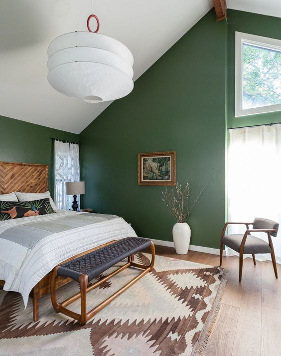 an attic mid-century modern bedroom with green walls, wood and rattan furniture, an oversized lamp and a printed rug