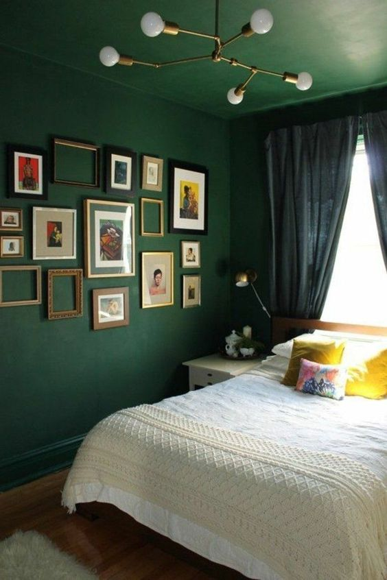 an eclectic bedroom with dark green walls and a ceiling, navy curtains, a gallery wall and bright bedding
