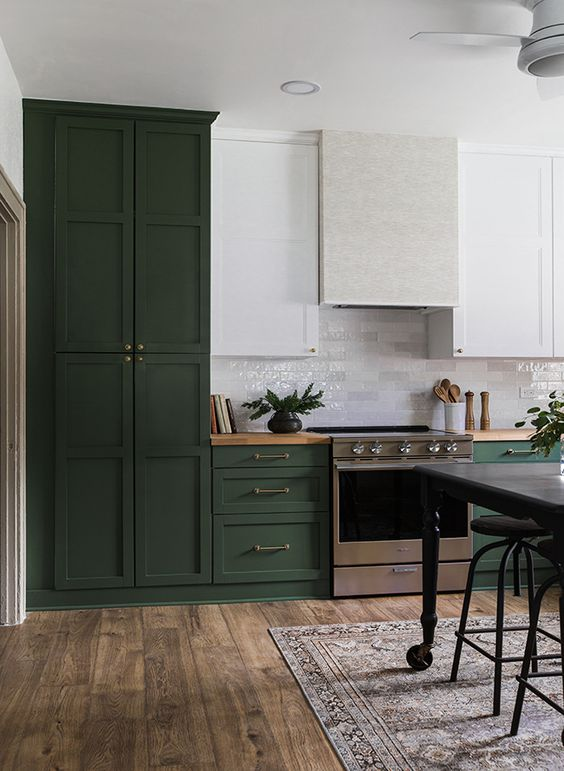 an eclectic kitchen in hunter green, with white upper cabinets and a subway tile backsplash and a white hood