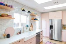 an eclectic kitchen with blush cabinets, a white tile backsplash, open shelves and colorful tableware
