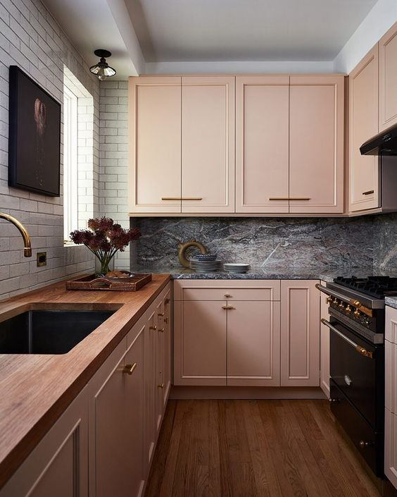 an eclectic kitchen with blush cabinets, a white tile wall, a grey marble backsplash and dark appliances